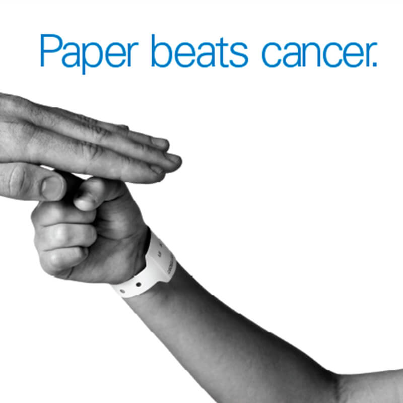 Hammermill store banner showing two hands playing rock-paper-scissors, the top hand winning and wearing a hospital armband, with the headline paper beats cancer
